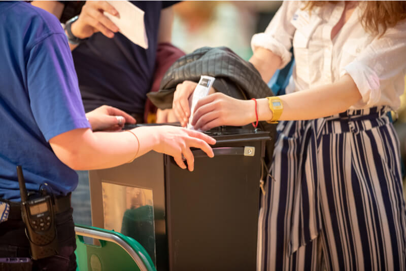 Image of a person in a white shirt and blue and white striped trousers putting a voting card into a ballot box being held by someone in a blue t-shirt.