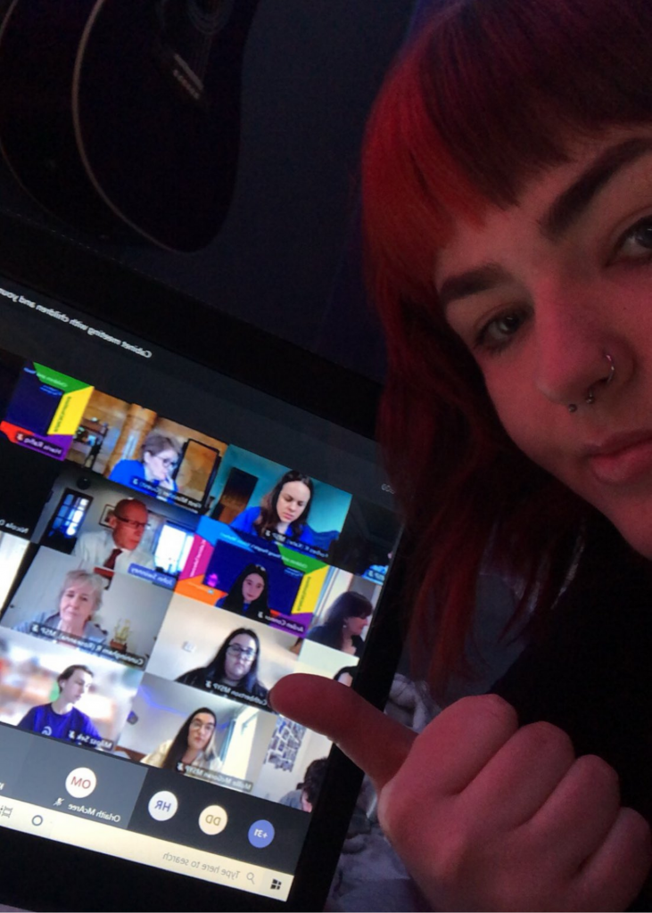 Selfie of Brooke Barr in front of a laptop showing the Cabinet meeting